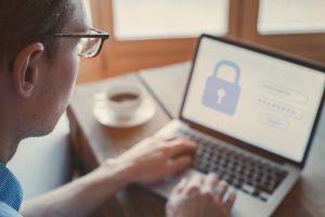 Silmälasipäinen henkilö kirjautuu sisään sovellukseen tietokoneen ruudulla. Käytöliittymässä näkyy iso lukon kuva.